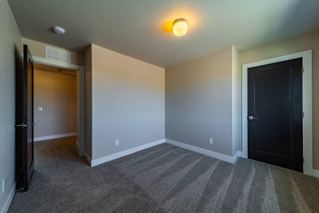 beige bedroom with black door
